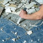 Worker remove, demolish old tiles in a bathroom with hammer and chisel